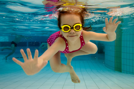 The-girl-smiles-swimming-under-water-in-the-pool